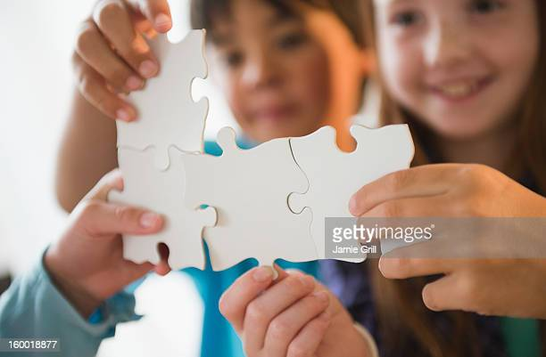 Close up of children's (8-9) hands holding jigsaw pieces