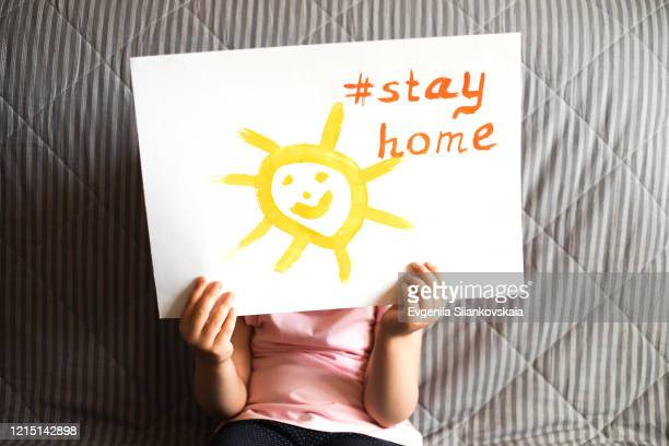 close up of child's hands holding a piece of paper with text stay home and sun. - 外出禁止令 ストックフォトと画像