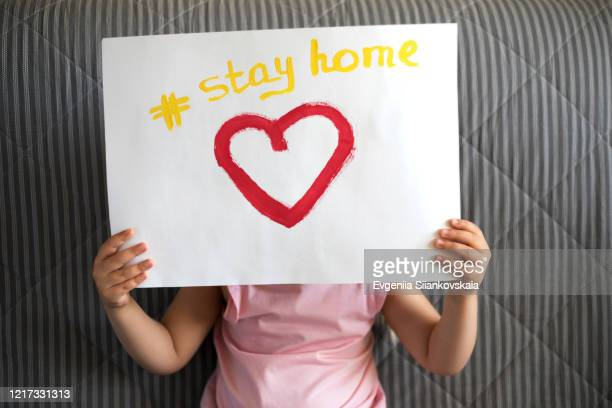 close up of child's hands holding a piece of paper with text stay home and red heart. - stay at home order stock pictures, royalty-free photos & images
