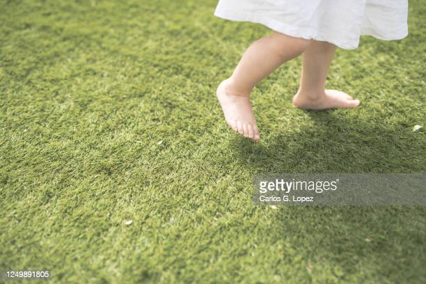 close up of child's legs walking on grass in sunny spring day - white dress stock pictures, royalty-free photos & images