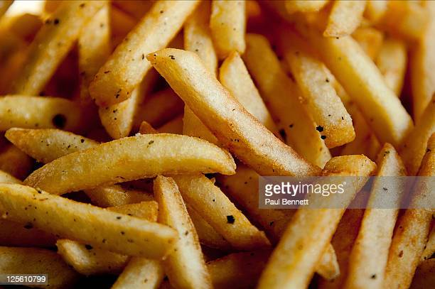 close up of chips fries with black pepper - fast food french fries stock pictures, royalty-free photos & images