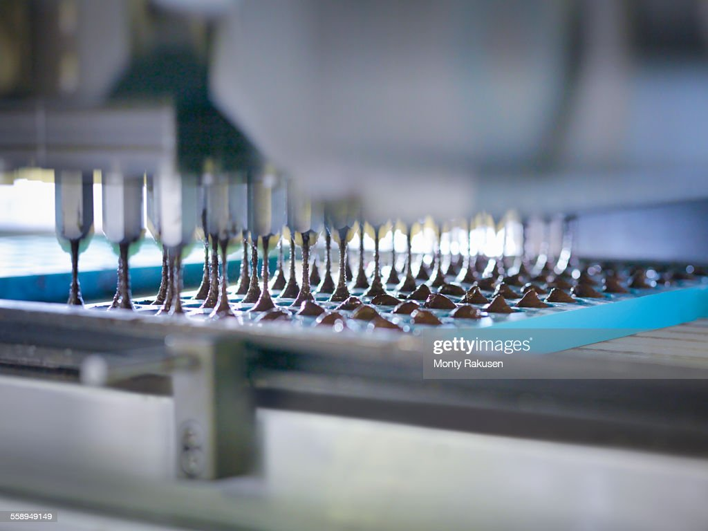 Close up of chocolate pouring into moulds in chocolate factory : Stock Photo