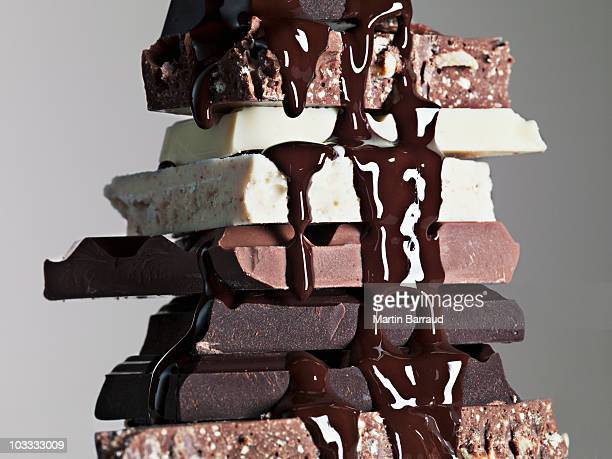 Close up of chocolate syrup dripping over stack of chocolate bars