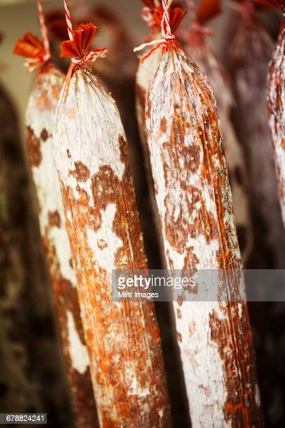 close up of chorizo sausages hanging from hooks in a charcuterie. - charcuteria fotografías e imágenes de stock