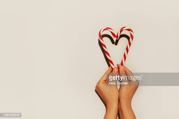 close up of christmas candy in heart shape in woman hands. valentine's day concept - valentine' day stock pictures, royalty-free photos & images