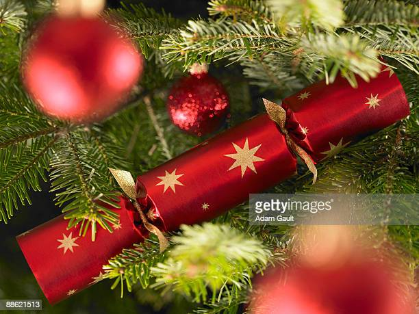 Close up of Christmas cracker and ornaments on tree