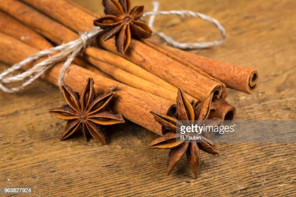 Close up of cinnamon sticks and star anise on rustic wood background