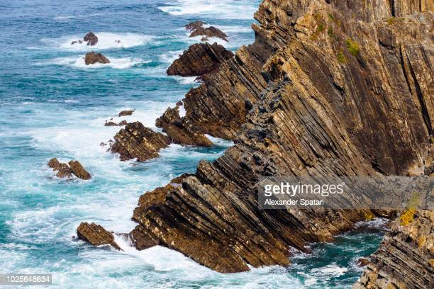 Close up of cliffs and ocean waves at Cabo Sardao, Beja, Portugal
