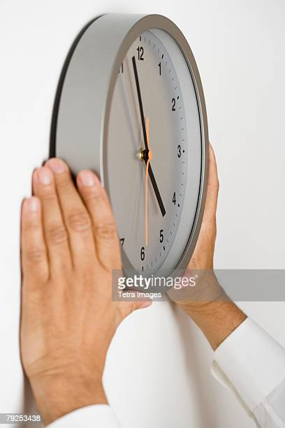 Close up of clock being put on wall
