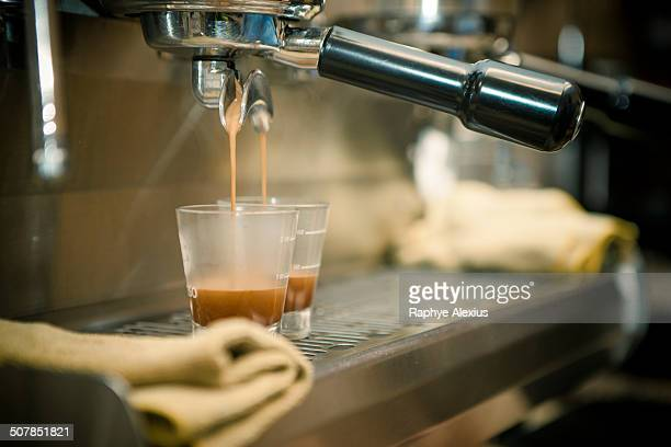 Close up of coffee machine pouring espresso in cafe