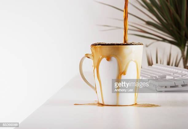 close up of coffee overflowing cup - excesso imagens e fotografias de stock