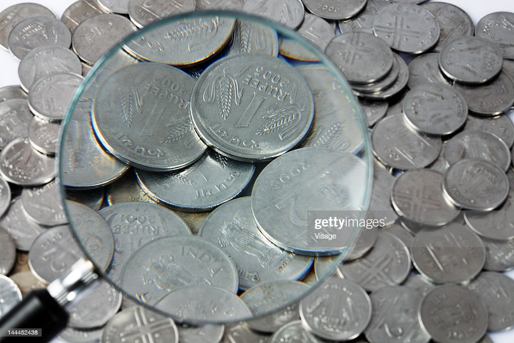 Close up of coins through magnifying glass : Stock Photo