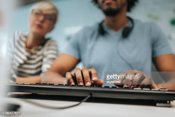 close up of colleagues typing an e-mail on computer keyboard in the office. - computer keyboard stock pictures, royalty-free photos & images