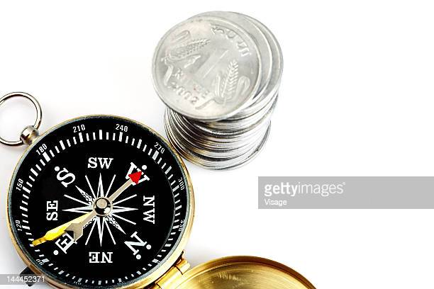 Close up of compass and one rupee coin