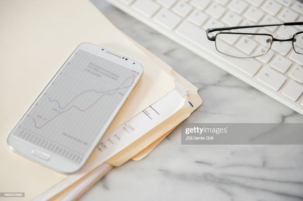 Close up of computer keyboard, files, cell phone and eyeglasses on office desk : Stock Photo