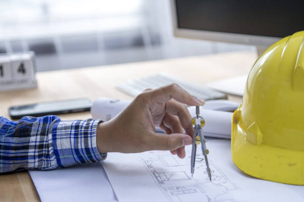 Close up of concentrated male engineer drawing hands working on architectural project at construction site at desk in office.