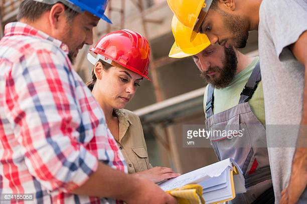 Close up of construction workers consulting the architect