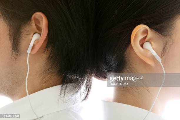 Close up of couple back to back sharing earphones