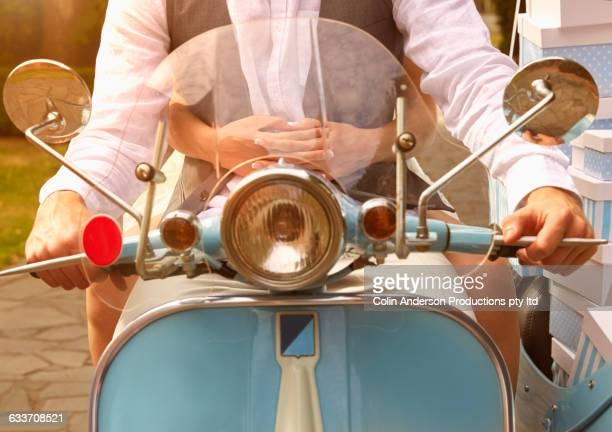Close up of couple driving vintage scooter