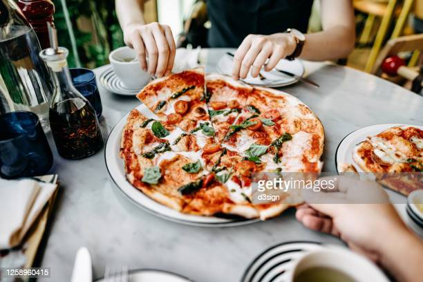 close up of couple getting and sharing slices of freshly made pizza and enjoying meal in an italian restaurant - mediterranean culture stock pictures, royalty-free photos & images