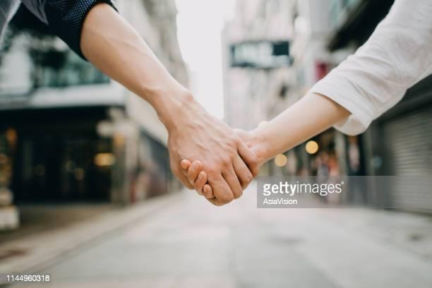 close up of couple holding hands against city street scene - darsi la mano foto e immagini stock