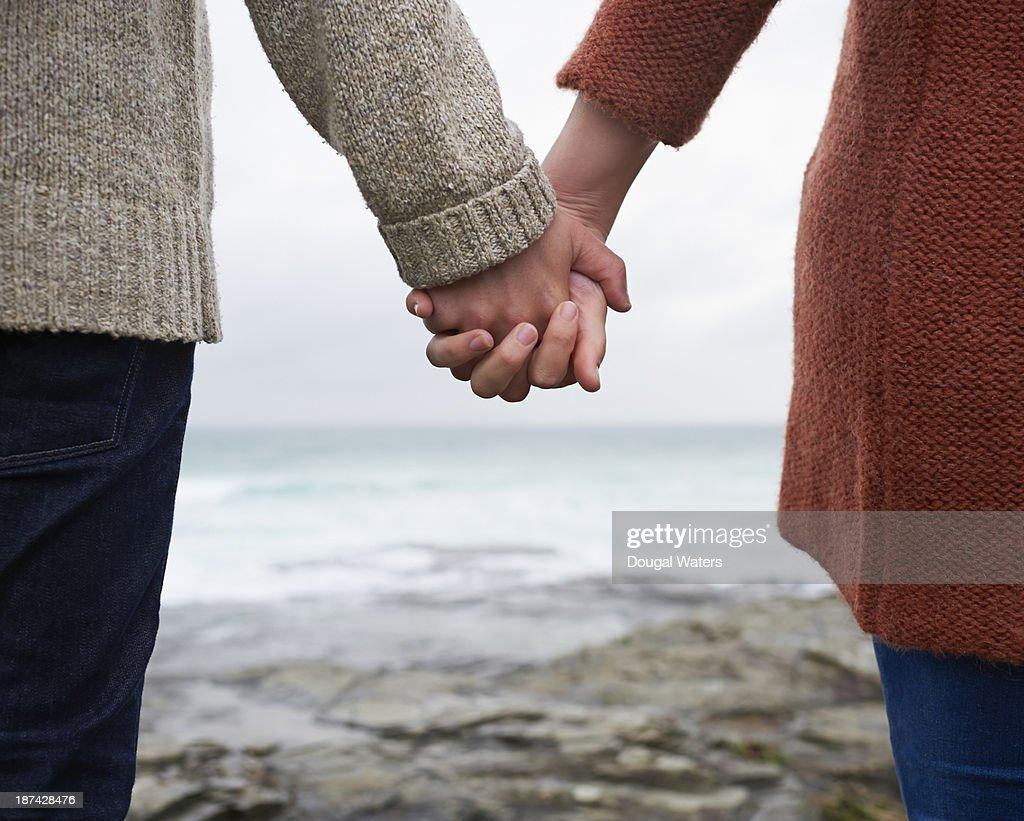 Close up of couple holding hands on coastline. : Stock Photo