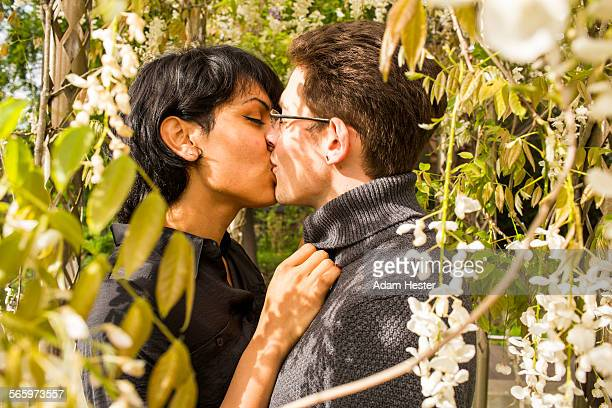 Close up of couple kissing in foliage