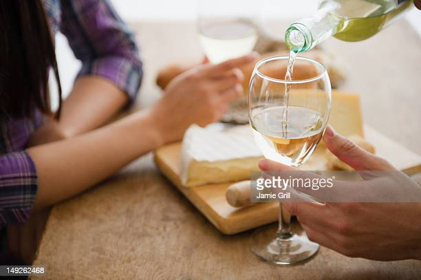 Close up of couple pouring wine and dining