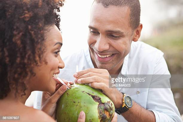 Close up of couple sharing coconut milk at beach, Rio De Janeiro, Brazil