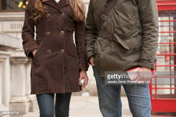 close up of couple standing near red phone booth, london, middlesex, united kingdom - red telephone box stock pictures, royalty-free photos & images