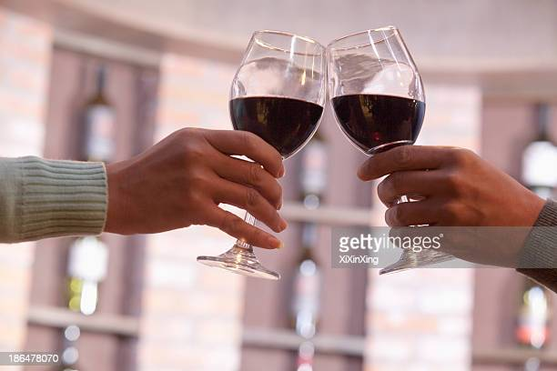close up of couple toasting, hands and wineglass only - ワイングラス ストックフォトと画像