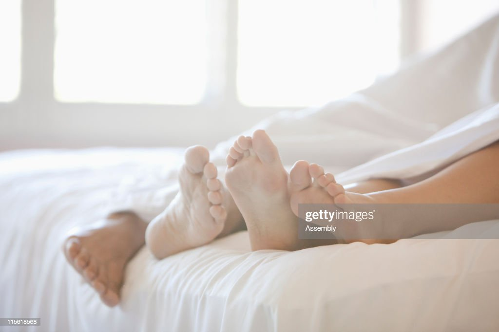 Close up of couple's feet in bed : Stock Photo