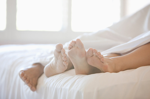 Close up of couple's feet in bed - gettyimageskorea