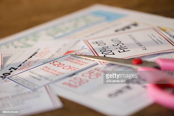 Close up of coupons and scissors on table