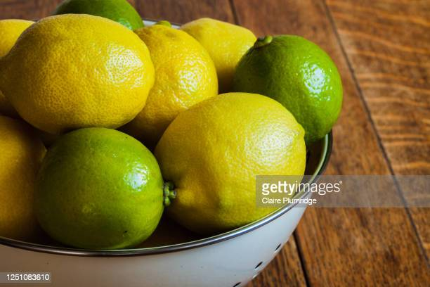 close up of cropped image of lemons and limes in a colander on a wooden table - newbury england stock pictures, royalty-free photos & images
