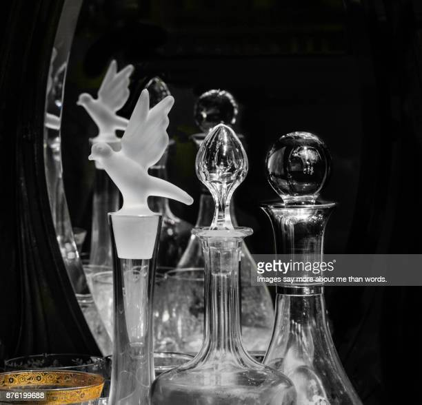 Close up of crystal objects like decanters and liqueur bottles.