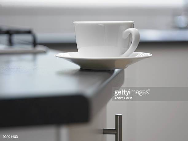 Close up of cup and saucer about to fall off counter