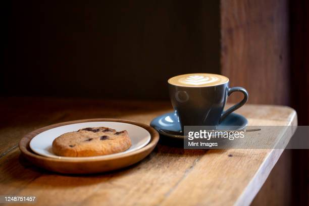 close up of cup of cappuccino and chocolate chip cookie on a plate in a cafe. - saucer stock pictures, royalty-free photos & images