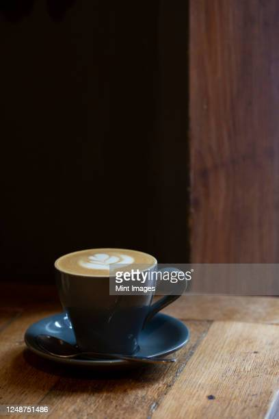 close up of cup of cappuccino on a rustic wooden table in a cafe. - saucer stock pictures, royalty-free photos & images