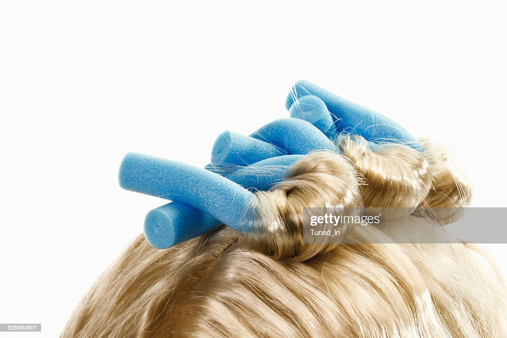 Close up of curlers on blonde wig : Stock Photo