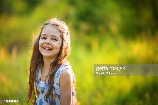close up of cute little girl looking at flowers on the meadow - solo una bambina femmina foto e immagini stock