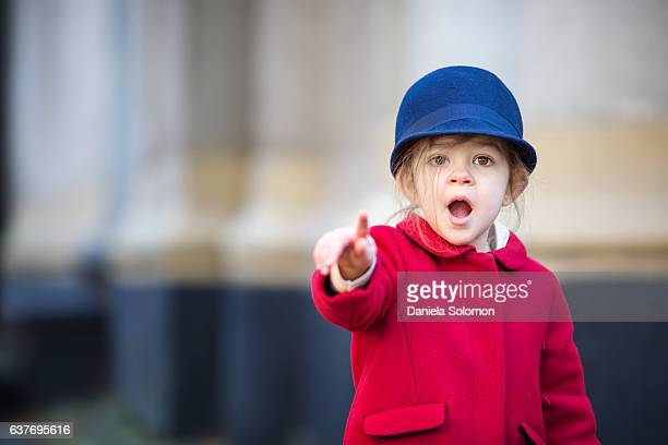 Close up of cute little girl with red coat and blue hat