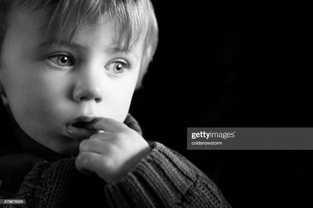 Close up of cute two year old caucasian little boy looking depressed and sad isolated on black background : Stock Photo