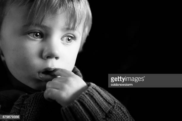 Close up of cute two year old caucasian little boy looking depressed and sad isolated on black background