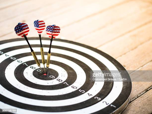 close up of darts on board over table - dartboard stock pictures, royalty-free photos & images