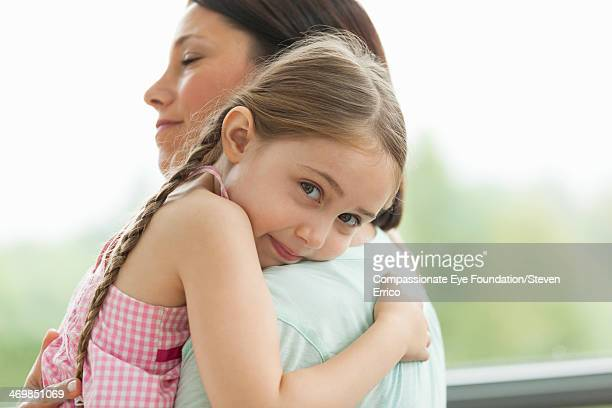 Close up of daughter hugging mother