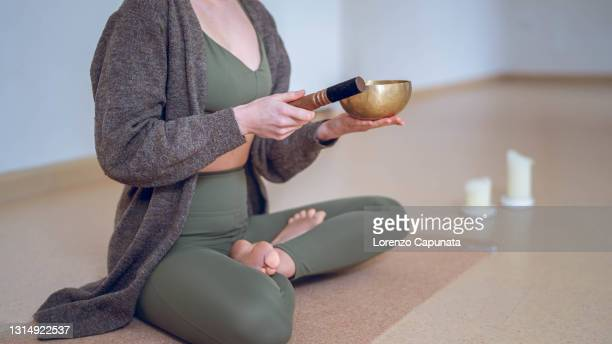 close up of details,  of an unrecognizable adult woman, sitting in an empty yoga room, making sounds with a brass chant and yoga stick - third place stock pictures, royalty-free photos & images