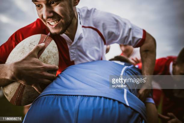 close up of determined athlete trying to get through his rivals on rugby match. - rugby league stock pictures, royalty-free photos & images