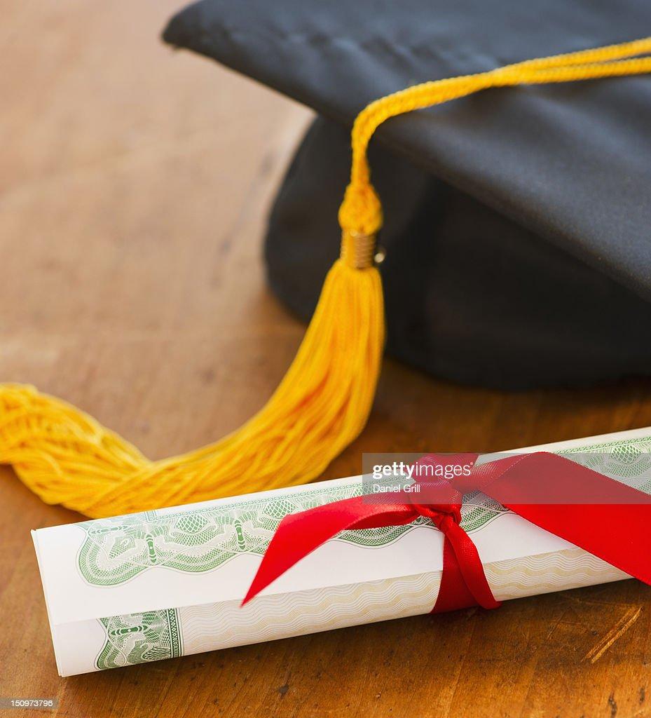 Close up of diploma and mortarboard, studio shot : Stock Photo