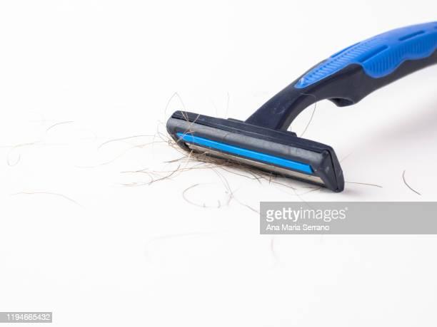 close up of disposable blue razor with hairs between the blades on a white background - schaamhaar stockfoto's en -beelden